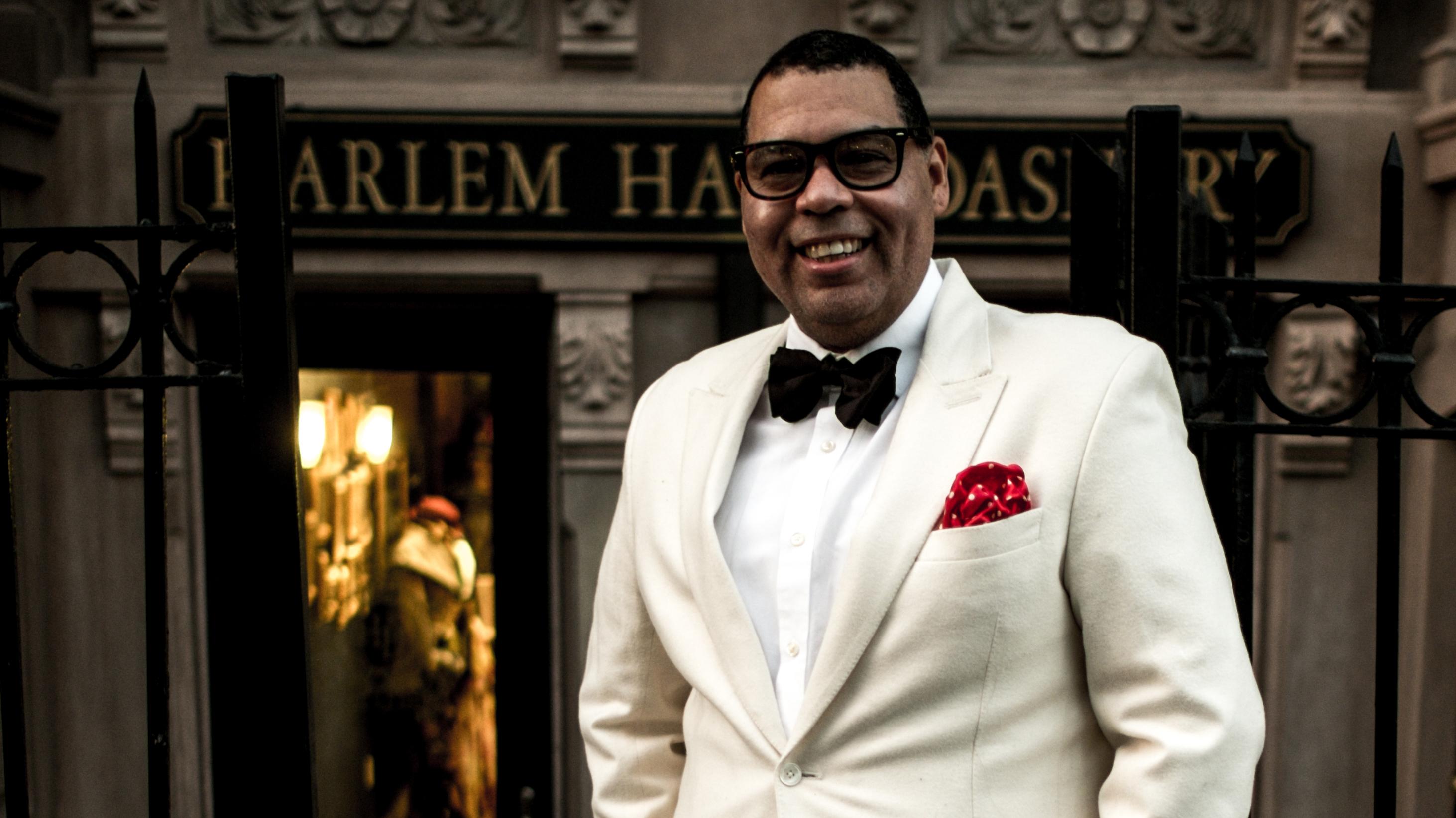 Guy Wood Sr., impecável em terno branco, à frente de sua Harlem Haberdashary