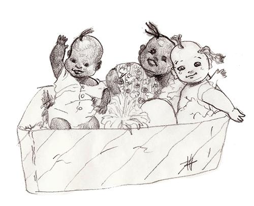Duas bonecas negras e uma boneca branca dentro de uma caixa de papelão.