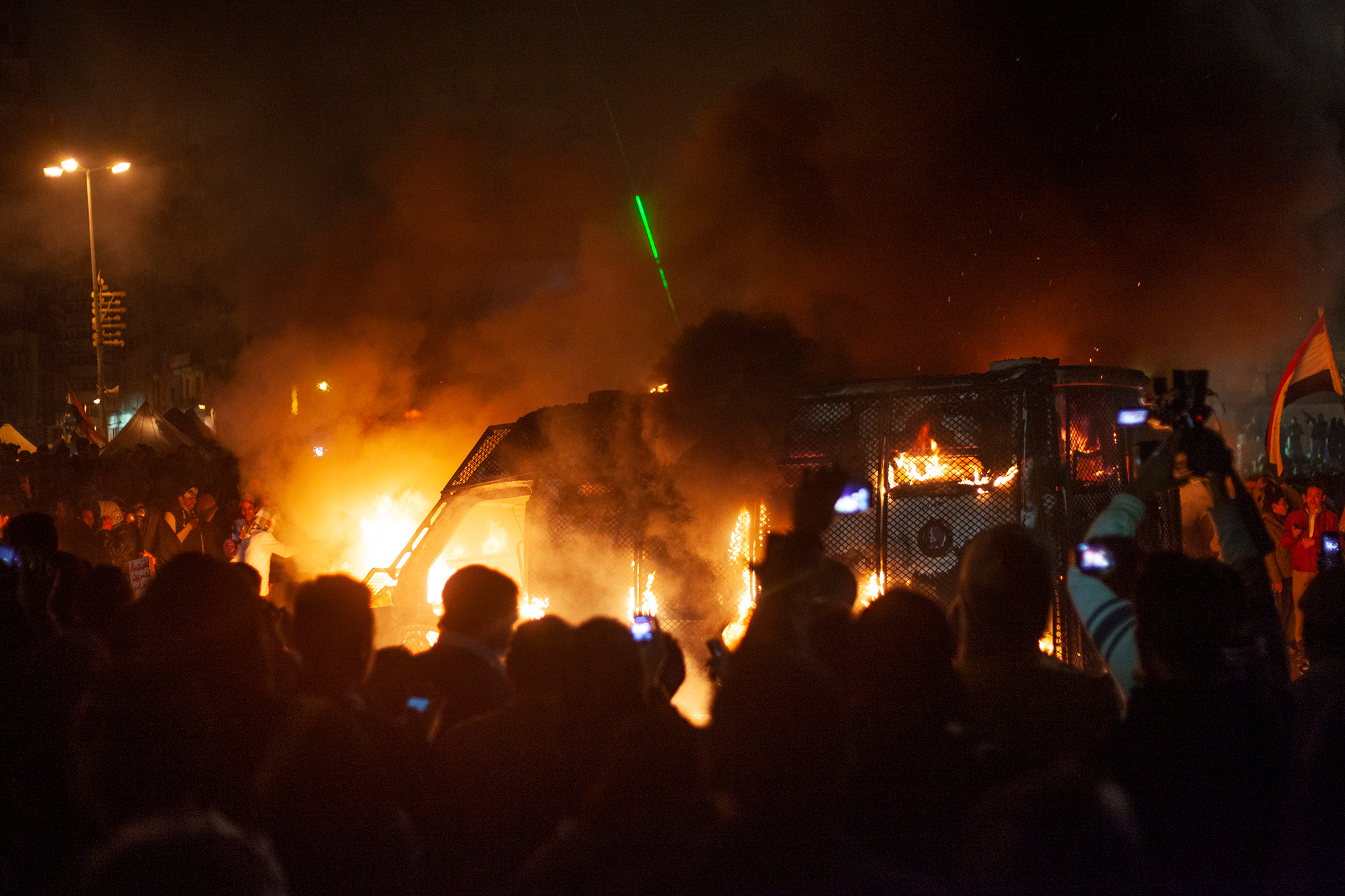 """Manifestantes ateando fogo em veículo da polícia egípcia durante manifestação na Praça Tahrir do segundo aniversário da Revolução Egípcia, em 28 de janeiro de 2013. Nessa data simbólica, os manifestantes protestavam efusivamente contra Mohamed Morsi, da Irmandade Muçulmana, presidente eleito no ano anterior. A intensidade da manifestação lembrou o revolucionário Ahmed Hassan das primeiras manifestações da Revolução Egípcia, lá em 2011, em que """"a primeira coisa que as milhões de pessoas que foram às ruas fizeram foi atear fogo nas delegacias, porque a polícia não nos tratava com dignidade""""."""