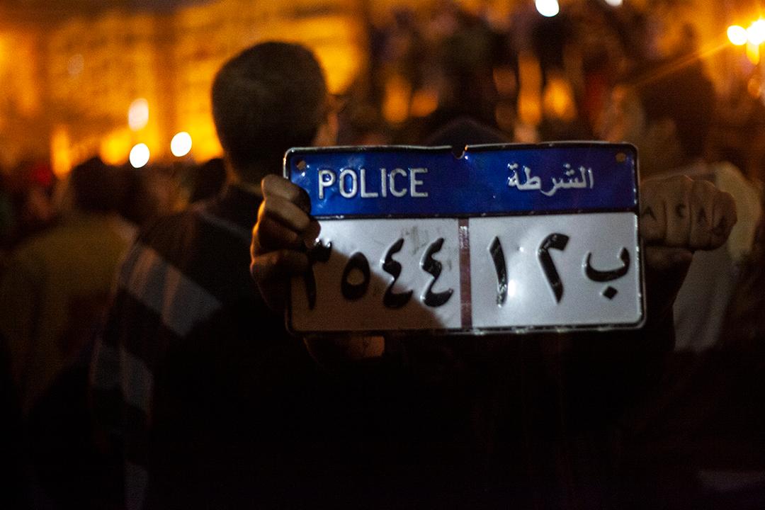"""Placa retirada de veículo policial queimado por manifestantes em protesto contra Mohamed Morsi em 28 de janeiro de 2013. Segundo o revolucionário Ahmed Hassan, havia um sentimento de """"transbordamento de raiva"""" nos manifestantes da Praça Tahrir nessa data, que marcava dois anos do começo da Revolução Egípcia. A insatisfação com o presidente se dava porque a Irmandade Muçulmana, grupo religioso que Morsi representava, 'sequestrou' a Revolução para chegar ao poder e, no final das contas, aplicaram a sua versão de governo repressivo."""