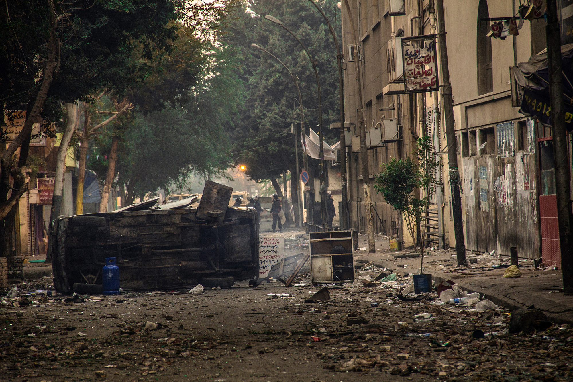 Escombros de um dos embates, ocorrido em 21 de novembro de 2011 na rua Muhammad Mahmoud, do confronto generalizado entre manifestantes e forças policiais que durou seis dias e foi o mais violento após a queda de Mubarak, com mais de 40 vítimas. O confronto se iniciou em 19 de novembro de 2021, após a polícia reprimir violentamente protesto pacífico de famílias no local em memória dos mortos da Revolução Egípcia de janeiro e fevereiro daquele ano. A rua e a Praça Tahrir foram o epicentro dos constantes embates entre população e tropas do governo desde o início da revolução.